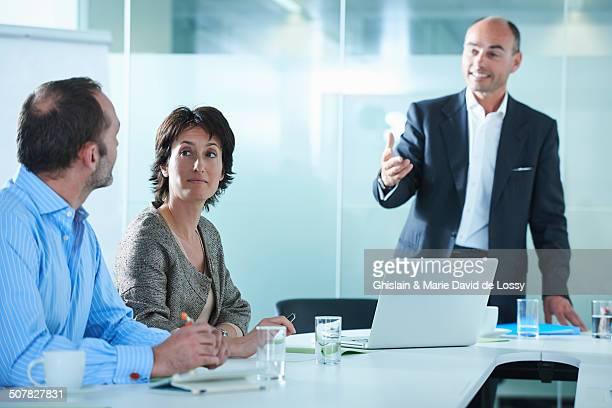 Businessmen and women arguing across boardroom table