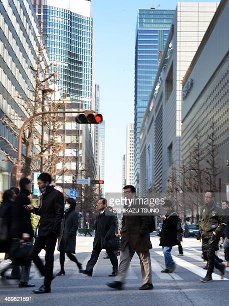 Businessmen and women cross a road in Tokyo on February 17, 2014. Japan's economy logged its best performance in three years as Premier Shinzo Abe's...