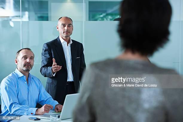 Businessmen and women debating across boardroom table