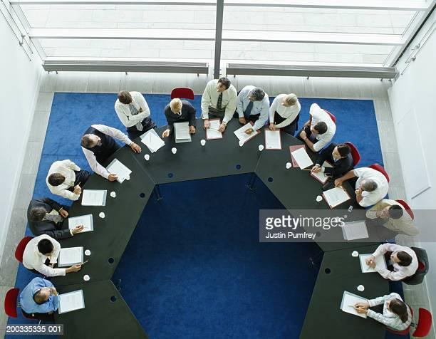 Businessmen and women in meeting at large round table, elevated view