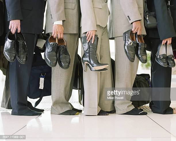 businessmen and women lining up, holding shoes, low section - five people stock pictures, royalty-free photos & images