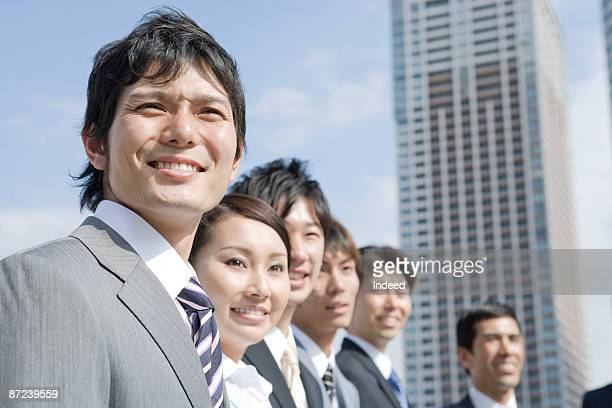 Businessmen and women smiling, looking away