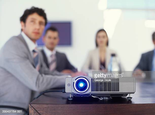 Businessmen and women watching film, projector on table