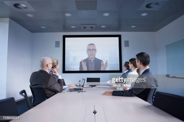 businessmen and women watching office conference call - symmetry stock pictures, royalty-free photos & images