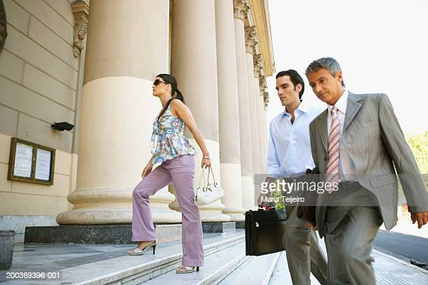 Businessmen and young woman walking up steps