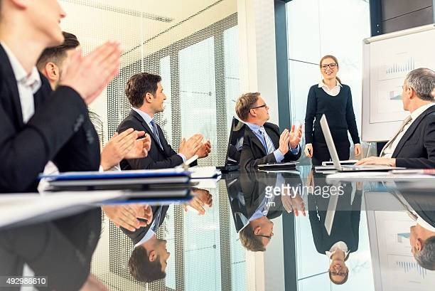 businessmen applauding a young businesswoman's presentation - executive director stock pictures, royalty-free photos & images