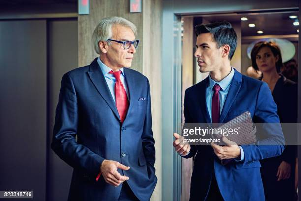 businessmen are exiting from the elevator in the company building discussing between them - executive director stock pictures, royalty-free photos & images