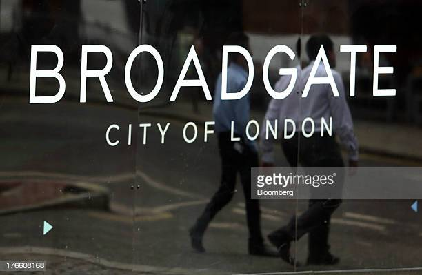 Businessmen are reflected in construction hoardings outside the building site at No 5 Broadgate in London UK on Thursday Aug 15 2013 UBS AG...