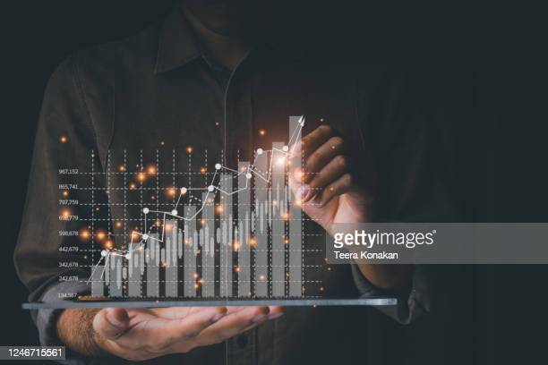 businessmen are using tablet computers to analyze trends of fast-growing businesses with rising graph bars on a black background. - economy stock pictures, royalty-free photos & images