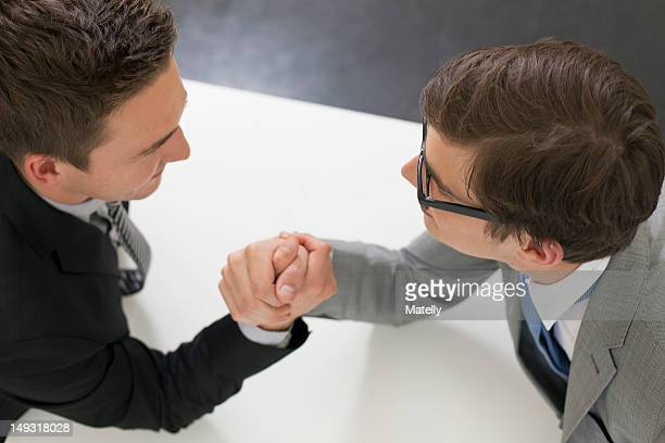 Businessmen arm wrestling in office