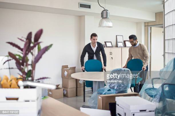 Businessmen arranging chairs in new office