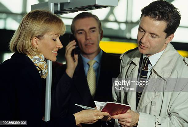 Businessmen at airport check-in desk with female airline employee