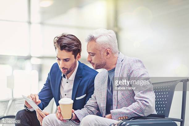 Businessmen at airport lounge using digital tablet