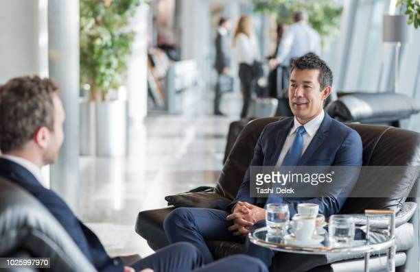 businessmen at airport waiting for a flight - gate stock pictures, royalty-free photos & images