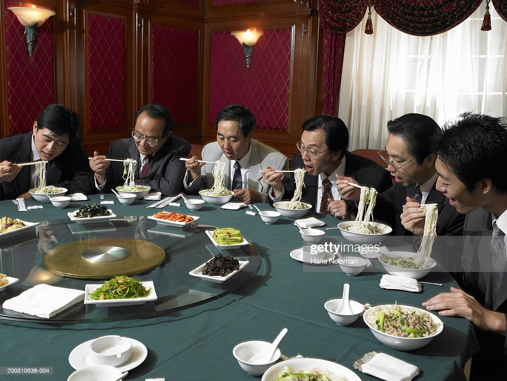 Businessmen at banquet table eating noodles : Stock Photo