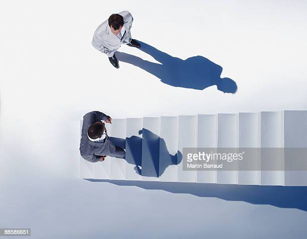Businessmen at bottom of stairway