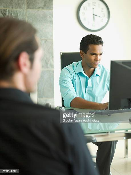Businessmen at computer in office