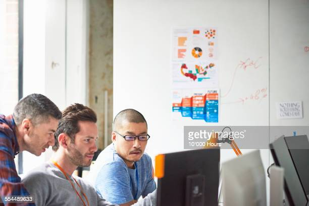 Businessmen at computer in tech start-up office