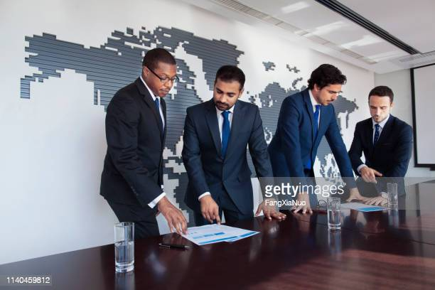 businessmen at conference table viewing documents - real estate developer stock pictures, royalty-free photos & images