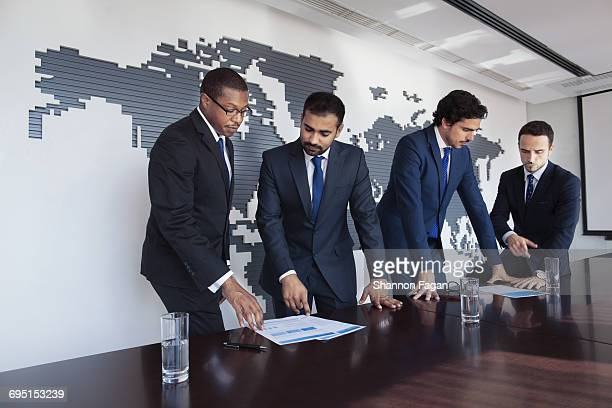 Businessmen at conference table viewing documents