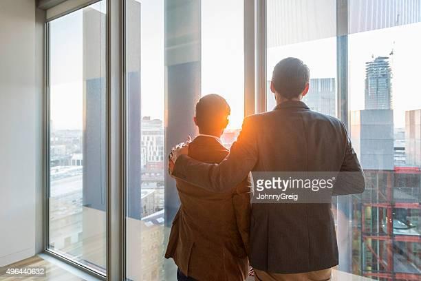 Businessmen at office window in sunlight, arm around