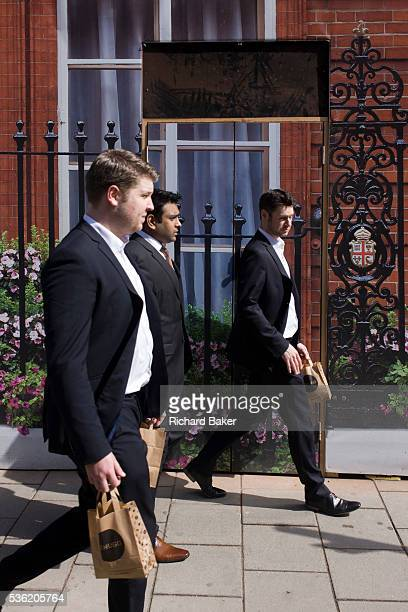 Businessmen bring back takeaway lunches walking past the construction hoarding belonging to Claridges in Mayfair Westminster Having collected their...