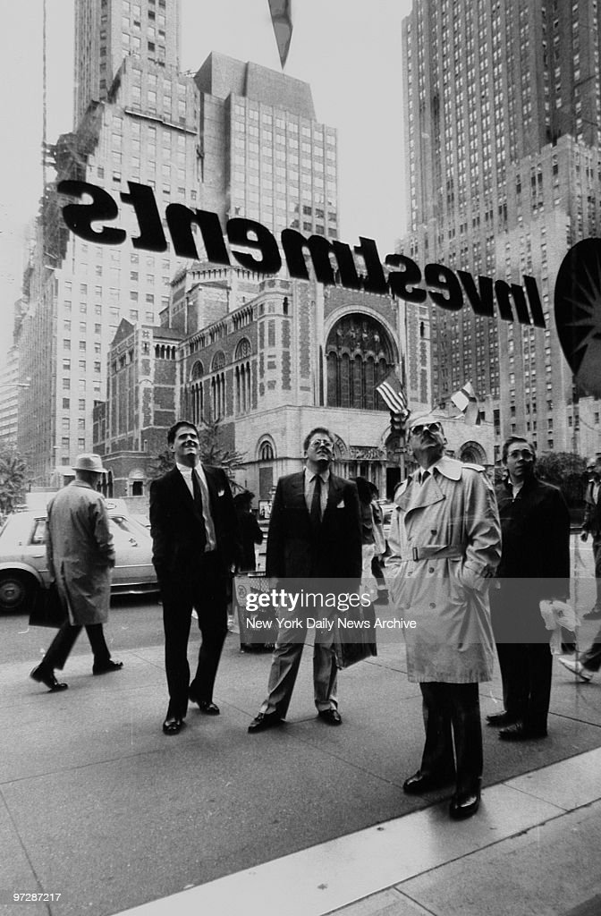 Businessmen, brokers and passersby look at quotations on screen on Black Monday at the Stock Exchange, Manhattan.