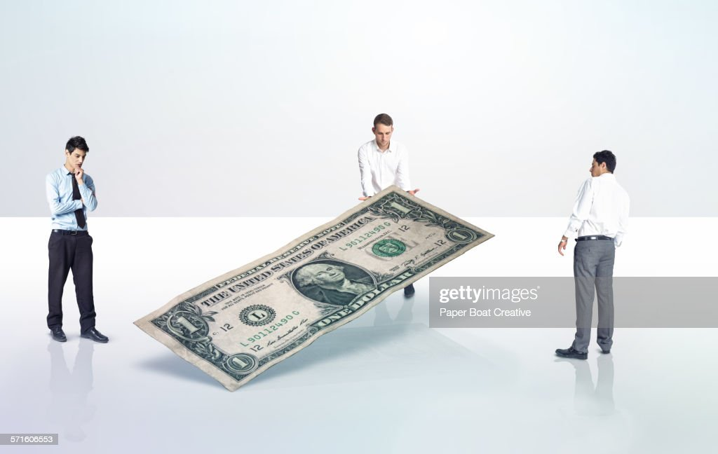 Businessmen carrying a dollar note : Stock Photo