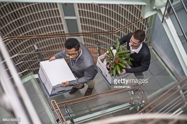Businessmen carrying belongings on staircase