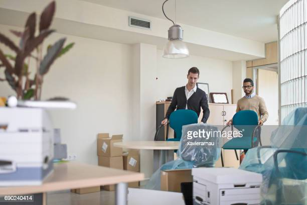 Businessmen carrying chairs in new office