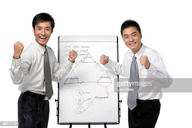 Businessmen celebrating by whiteboard