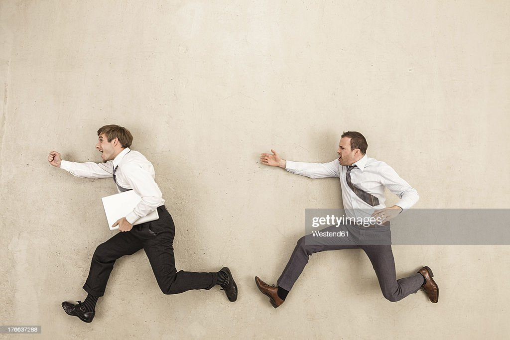 Businessmen chasing against beige background : Stock Photo