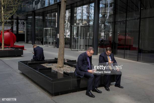 Businessmen check messages outside a financial institution in the Square Mile, the capital's financial district, on 3rd March 2017, in the City of...