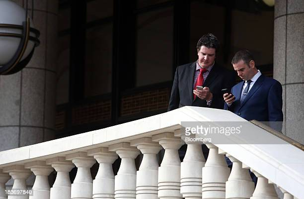 Businessmen check their mobile devices in the city of London UK on Wednesday Oct 9 2013 UK industrial production unexpectedly fell the most in almost...