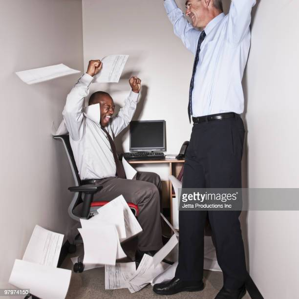 Businessmen cheering in small office