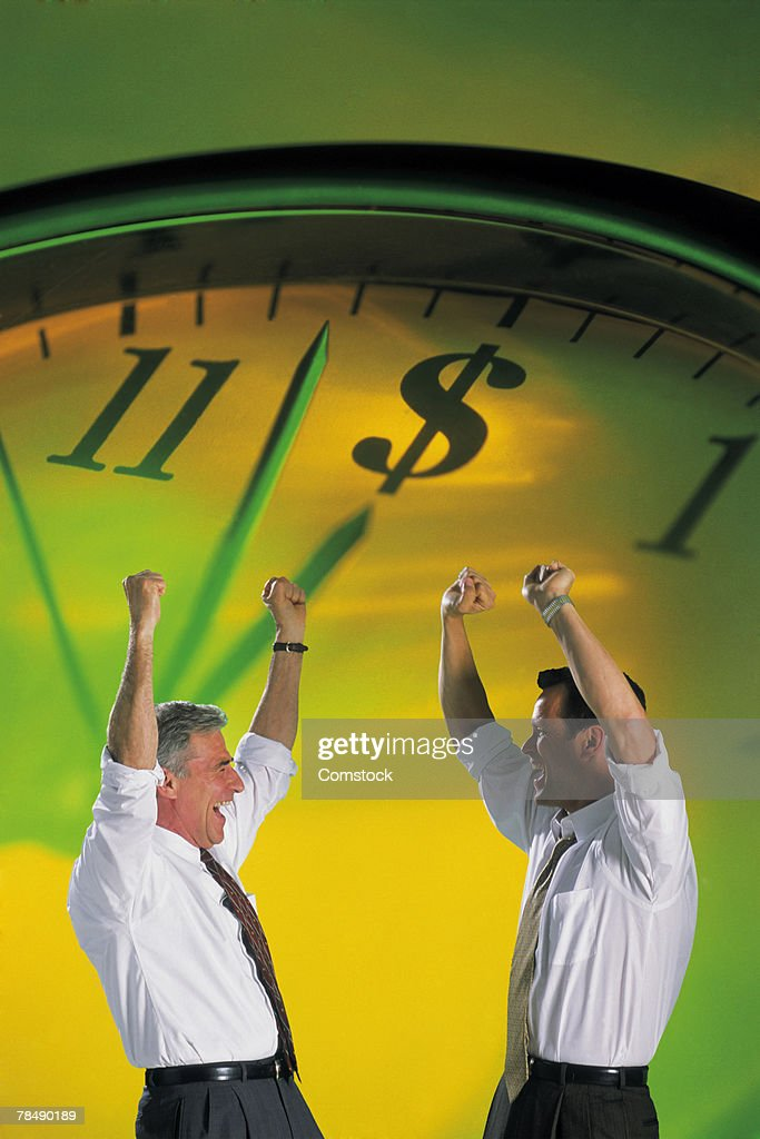 Businessmen cheering with clock : Stock Photo