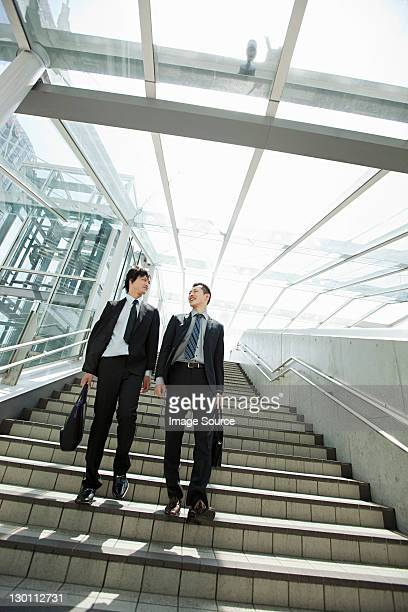 Businessmen coming down steps