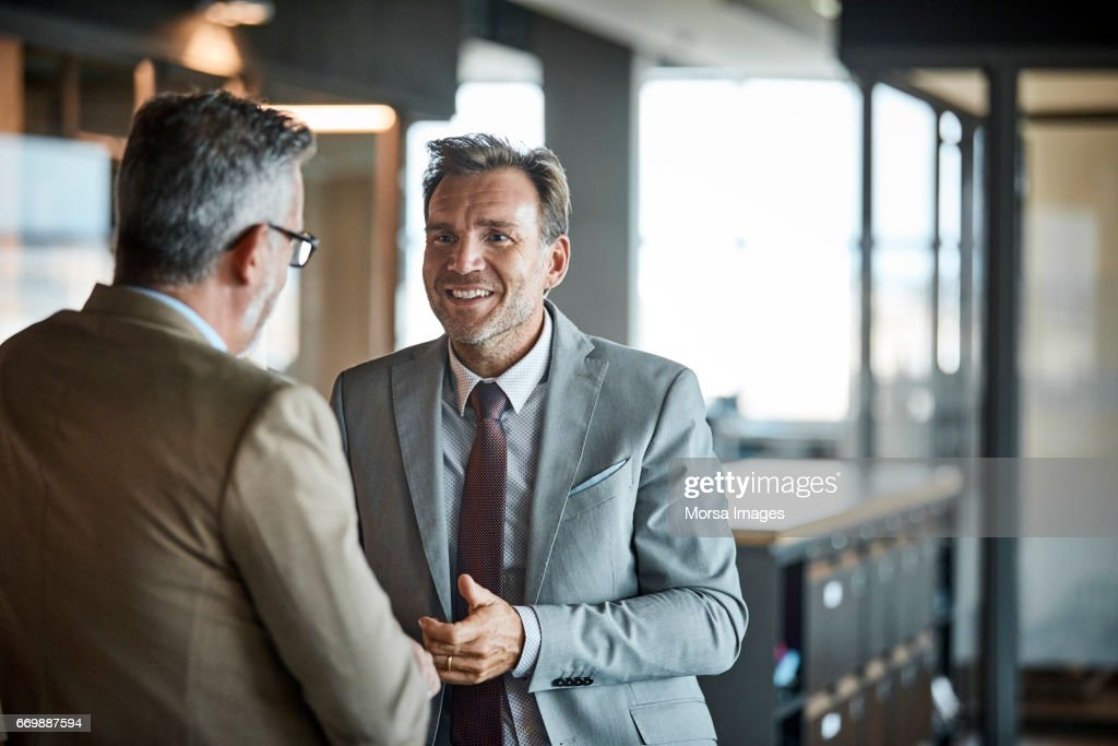 Businessmen communicating in textile factory : Stock Photo