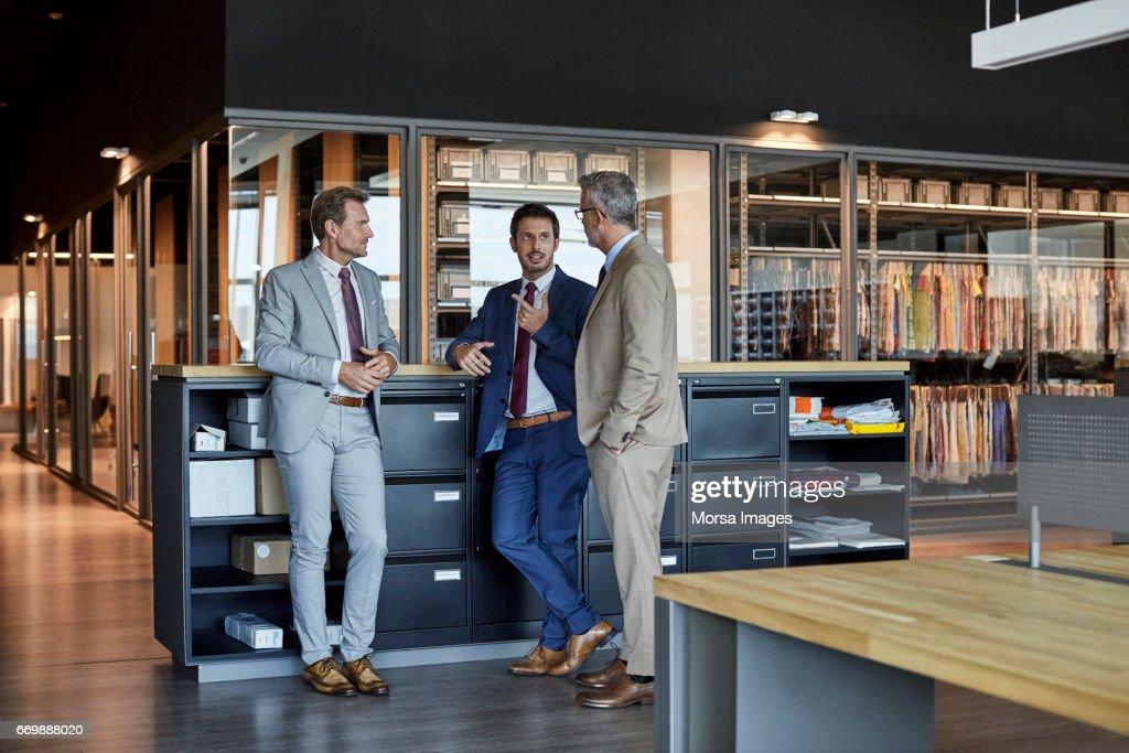 Zakenlieden communiceren in textielfabriek : Stockfoto