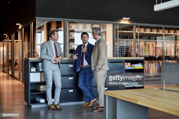 businessmen communicating in textile factory - three people stock pictures, royalty-free photos & images