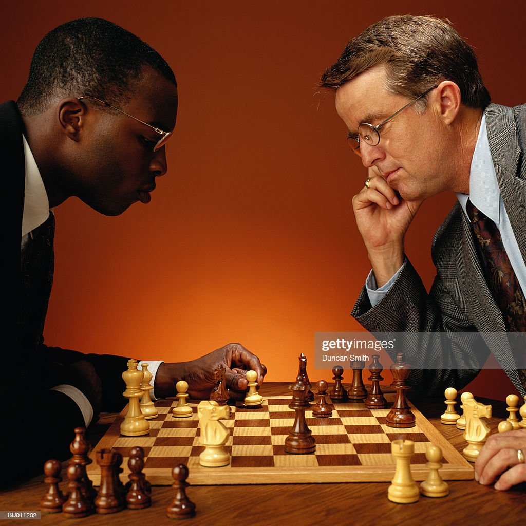 Businessmen Concentrating on a Chess Game : Stock Photo