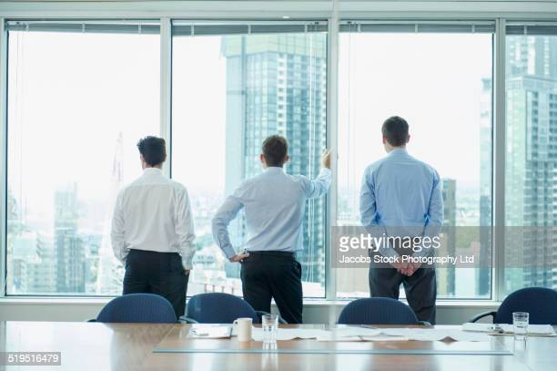 Businessmen contemplating cityscape from office window