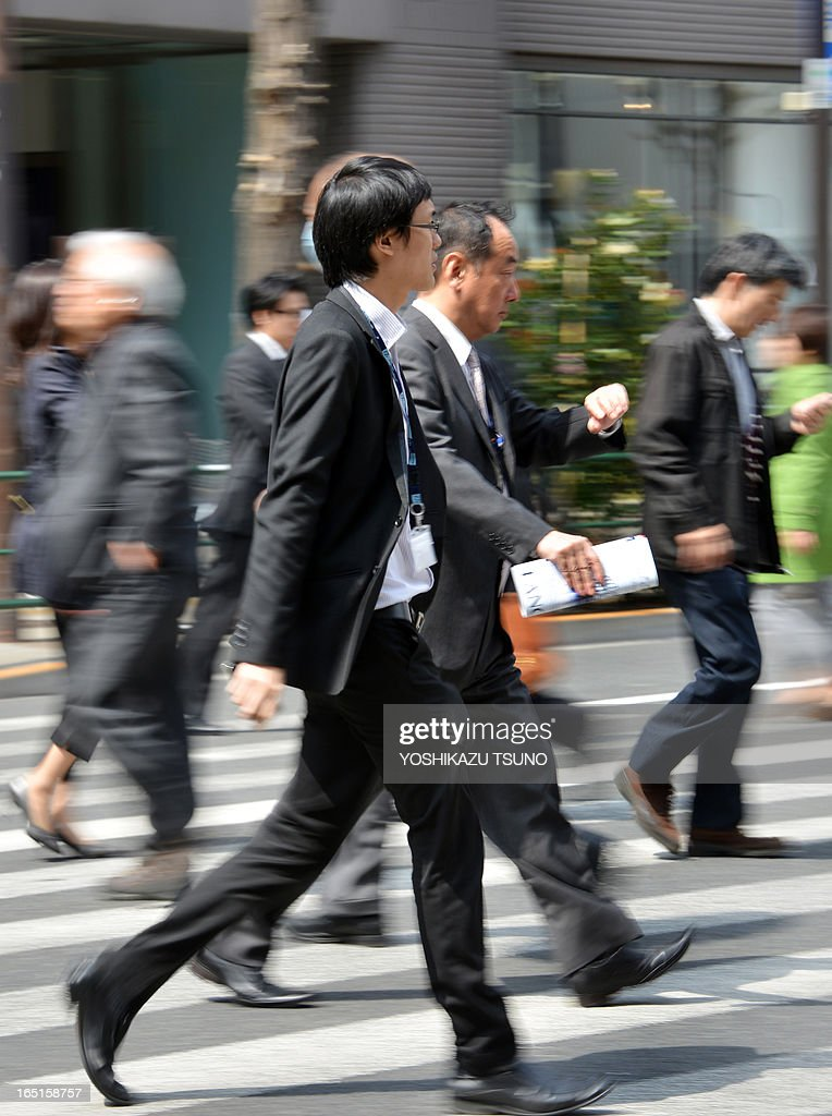 Businessmen cross a road in Tokyo on April 1, 2013. Confidence among large Japanese manufacturers improved in the first quarter, a central bank survey showed on April 1, as Tokyo works to reverse years of limp growth in the world's third-largest economy. AFP PHOTO / Yoshikazu TSUNO