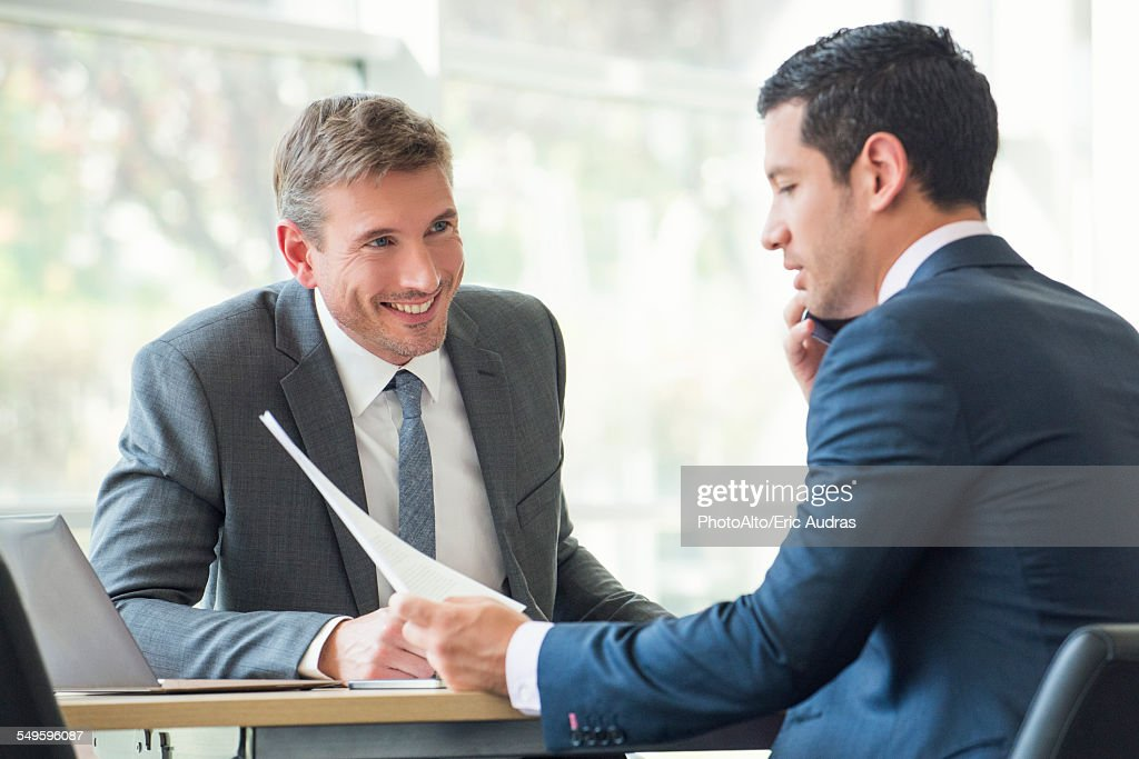 Businessmen discussing documents in meeting : Stock Photo