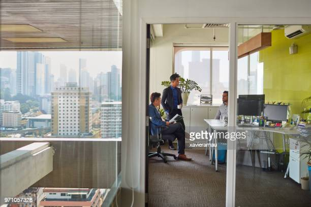 Businessmen discussing during meeting at cubicle