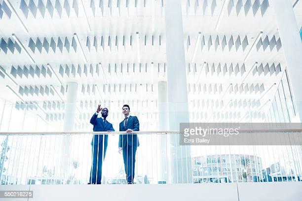 Businessmen discussing ideas in open plan office
