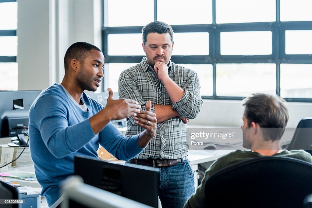 Businessmen discussing in creative office : Stock Photo