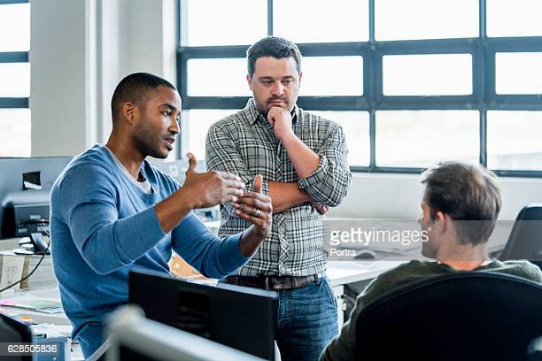 Businessmen discussing in creative office