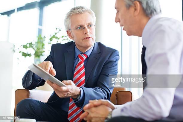 Geschäftsleute diskutieren Informationen auf tablet PC