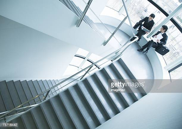 Businessmen discussing on staircase landing